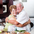 Senior couple hugging in kitchen — Stock Photo #10254274
