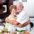Senior couple hugging in kitchen — Stock Photo