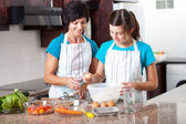 Mother teaching teen daughter baking — Stock Photo