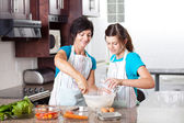 Teen daughter helping mother in kitchen — Stock Photo