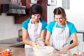 Happy mother and teen daughter baking — Stock Photo