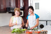 Middle aged woman cooking with senior mother — Stock Photo
