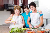 Teen girl watching mother and grandmother cooking — Stock Photo