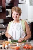 Happy senior woman cooking — Stock Photo