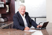 Happy senior man checking investment online — Stock Photo