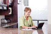 Senior woman using internet banking — Stock Photo