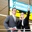 Stock Photo: Business travellers checking boarding information
