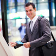 Stock Photo: Businessman using self check in machine