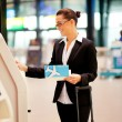 Businesswoman using self help check in machine — Stock Photo