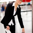Stock Photo: Businesswoman checking size of carry-on luggage
