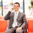 Businessman talking on mobile phone at airport — Stock Photo