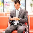 Royalty-Free Stock Photo: Businessman sending text messages at airport