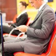 Stock Photo: Businessmsending text messages at airport