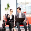 Business travellers waiting for flight at airport - Stock Photo