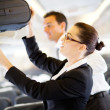 Flight attendant helping passenger with luggage — Stock Photo #10422835