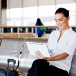 Young businesswoman using tablet computer at airport — Stock Photo