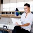 Young businesswoman using tablet computer at airport — Stock Photo #10422903