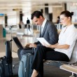 Business travellers waiting for flight - ストック写真