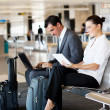 Business travellers waiting for flight - Stock Photo