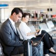 Businessman and businesswoman using computer at airport — Foto de Stock
