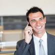 Happy businessman talking on cell phone at airport — Stock Photo