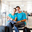 Happy young couple waiting for flight — Stock Photo