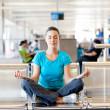 Young woman doing yoga meditation at airport — Stock Photo