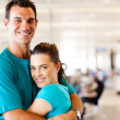 Happy young couple hugging at airport — Stock Photo