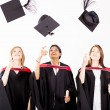 Group of female graduates throwing graduation cap — Stock Photo