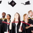 Stock Photo: Graduates throwing caps