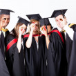 Stock Photo: Group of graduates looking through their diploma