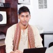 Young indian man using computer at home — Stock Photo