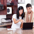 Young indian couple using computer - Stock Photo