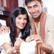 Indian couple put coin in piggybank — Stockfoto