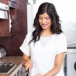Stock Photo: Young woman cooking in kitchen