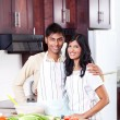 Happy young indian couple in kitchen — Stock Photo #10423520