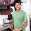 Happy young man cooking — Stock Photo