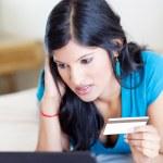 Young woman checking credit card balance — Stock Photo