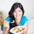 Cheerful young woman eating fruit salad — Stock Photo #10423626