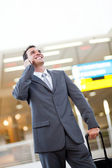 Businessman talking on cellphone at airport — Stock Photo