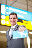 Happy businessman presenting air ticket — Stock Photo