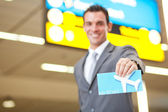 Young businessman presenting air ticket — Stock Photo