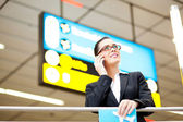 Businesswoman talking on cell phone at airport — Stock Photo