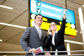 Business travellers checking boarding information — Stock Photo