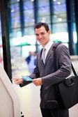 Businessman using self check in machine — Stock Photo