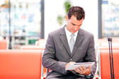 Businessman using tablet at airport — Stock Photo
