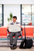 Businessman reading newspaper at airport — Stock Photo