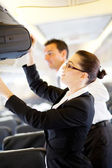 Flight attendant helping passenger with luggage — Stock Photo