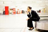 Kobieta siedzi na przenośnik taśmowy i czekam na jej bagażu — Zdjęcie stockowe