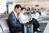 Empresário e mulher de negócios usando o computador no aeroporto — Foto Stock